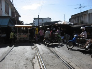 The train market sits on the train tracks until the train comes and then they close their canopies and move their goods to allow the train to pull in and stop. They then sell to the people on the train.