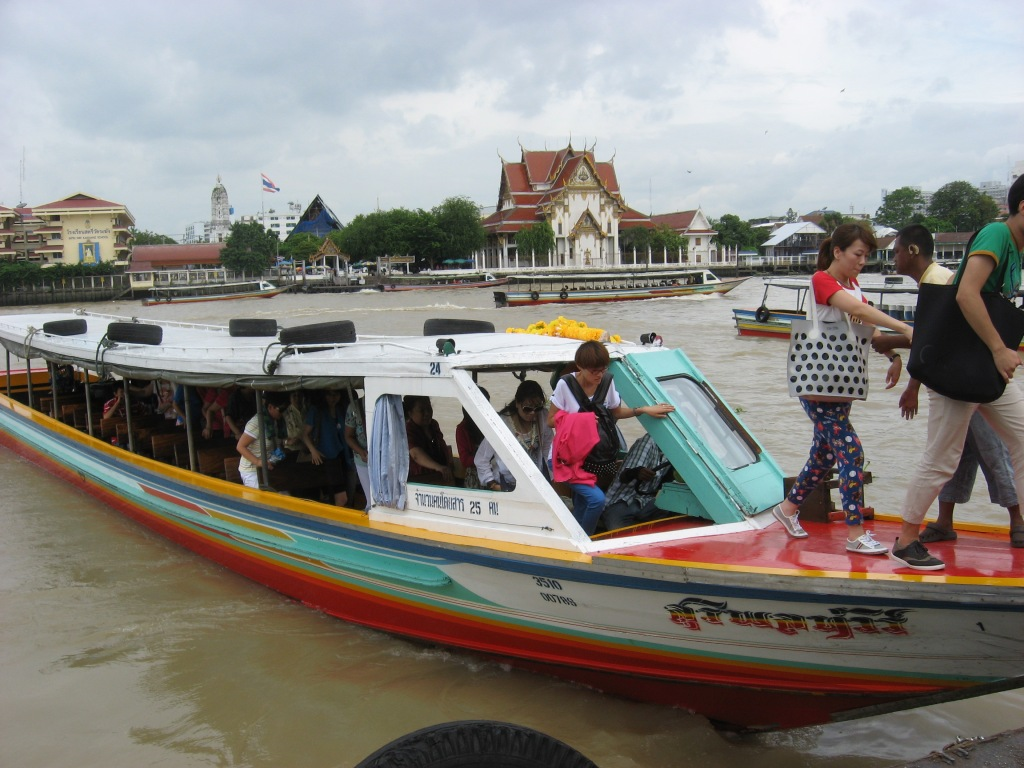 Tourist group boats on river thru Bangkok